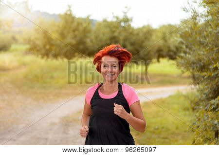 Happy Healthy Woman Jogging Along Outdoor Pathway