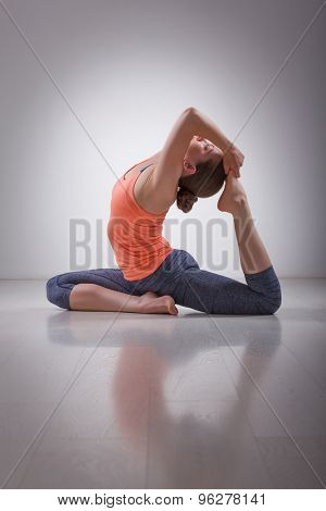Beautiful sporty fit yogini woman practices yoga asana Eka pada rajakapotasana - one-legged king pigeon pose in studio