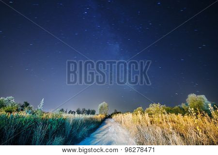 Milky Way and stars above road in a field