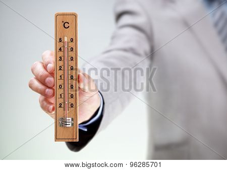 Businessman holding thermometer measuring high temperature concept for climate, stress, under pressure or deadline