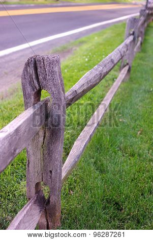 Split rail fence at edge of grassy pasture meets up with blacktop road, both trailing off into the distance. poster