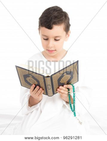Muslim Young Boy Reading Quran And holding Rosary