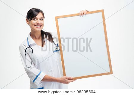 Smiling medical doctor holding blank board isolated on a white background. Looking at camera