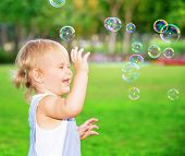 Happy child having fun in the park, cute blond baby girl playing with soap bubbles on the yard, joyful little kid enjoying outdoors game poster