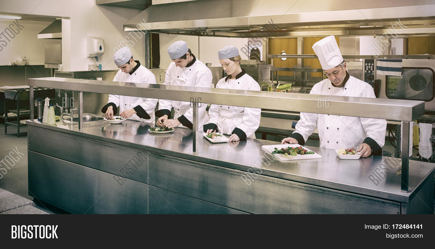 Focused chefs preparing plate in professioanl kitchen