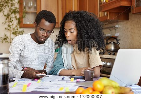 African Male In Glasses Calculating Family Expenses Holding Cell Phone, His Surprised Wife With Curl