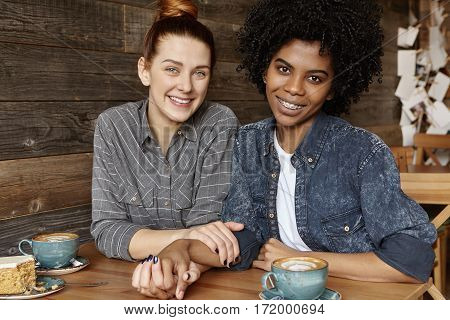 Candid Indoor Shot Of Cute Homosexual Couple Holding Hands And Looking At Camera With Happy Smiles,