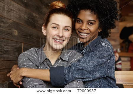 Happy Young Interracial Homosexual Couple Spending Nice Time Together At Modern Coffee Shop. African