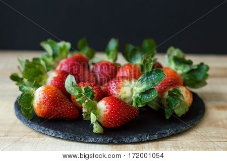 Black slate board with fresh strawberry on wooden table selective focus