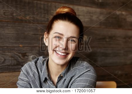 Headshot Of Cute Girl With Hair Bun Spending Lunch Break At C Restaurant With Wooden Walls, Sitting