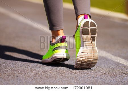 Runner Feet Running On Road Closeup On Shoe. Woman Fitness Jog Workout Welness Concept.