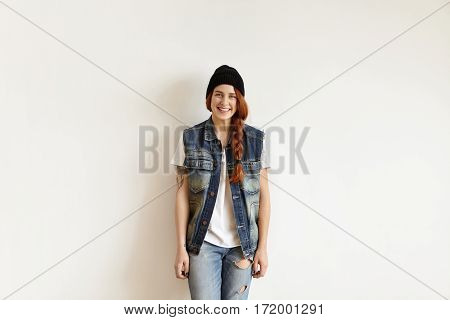 Isolated Studio Portrait Of Stylish Caucasian Girl Dressed In Trendy Clothes Standing At White Wall