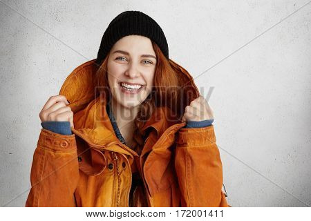Headshot Of Attractive Young Caucasian Woman With Charming Smile Wearing Trendy Winter Clothes Keepi