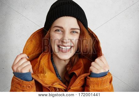 Close Up Portrait Of Attractive Girl With Ginger Hair Adjusting Hood Of Red Winter Coat Looking At C