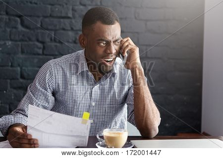 Angry African Businessman In Formal Shirt Having Furious Look, Holding Piece Of Paper, Yelling At Mo