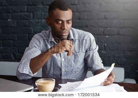 Successful African Entrepreneur Studying Documents With Attentive And Concentrated Look, Drinking Co