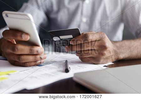 Modern Technology And Online Shopping. African Man In Shirt Paying For Goods On Internet Using Credi
