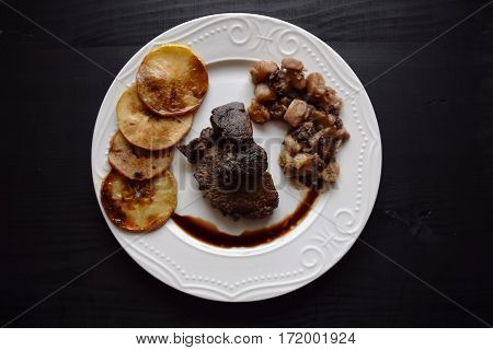 Wild boar meat with roasted apples, and roasted vegetables,served on a porcelain plate.