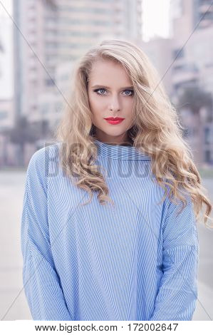Portrait of young blond female with trendy make up with red lips and smoky eyes and long curly hair