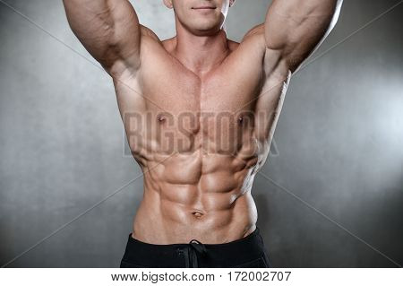 Brutal Strong Bodybuilder Man Posing In Studio On Grey Background