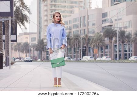 Young blond woman with long curly hair trendy make-up in blue blouse yellow shoes and with green handbag standing at busy street in Dubai downtown