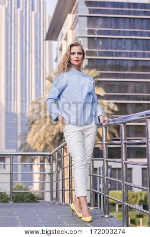 Young business woman with long blond hair and trendy make up standing near metal bridge. Positive and friendly woman standing in front of Dubai skyscrapers in the UAE