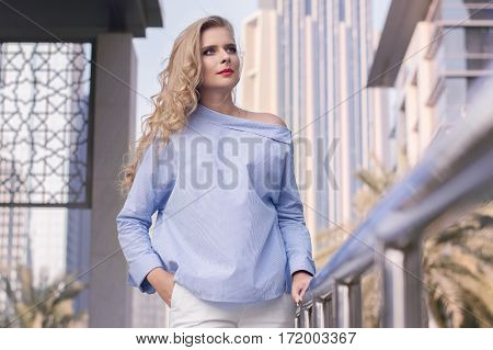 Blond female with long curly hair and trendy and fashionable make up standing at Dubai street in the UAE. Business portrait. Young business woman