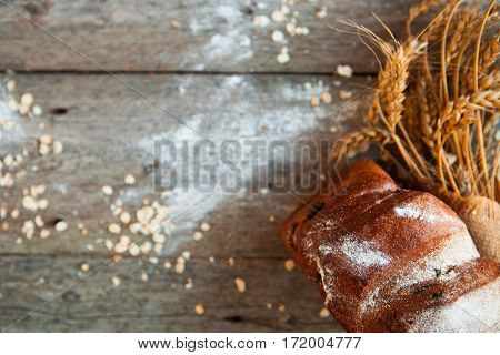 Rustic Bread And Wheat On An Old Vintage Planked Wood Rustic Table. Dark Moody Background With Free