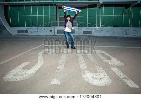 Female Holding Skateboard Above Head