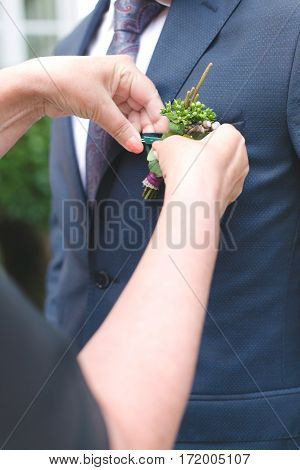 Mom adds boutonniere for the groom's suit close-up