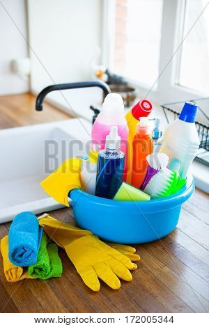 Basket With Cleaning Items On Blurry Background White Citchen. Cleaning Concept.