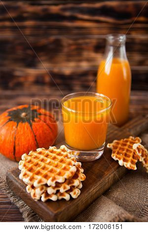 Bottle And Glass Of Fresh Pumpkin Juice With Wafer And Pumpkin On Dark Wooden Table. Selective Focus