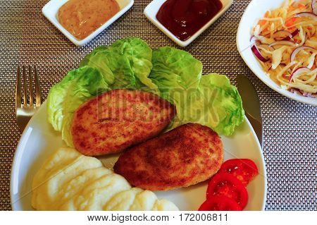 Two chicken cutlets with coleslaw, gravy boat with mustard and ketchup.