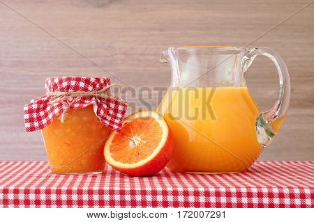 Orange juice and jam on a red checkered tablecloth.Wooden background