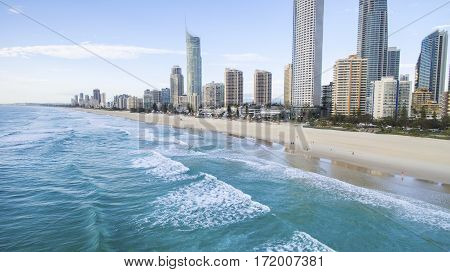 Aerial view of over the surf of Gold Coast cityscape and famous beach.