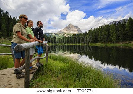 Happy family with teenager taking brake during trekking day on Dolomites mountain in summer time in Italy. Concept of travel, friendly family.