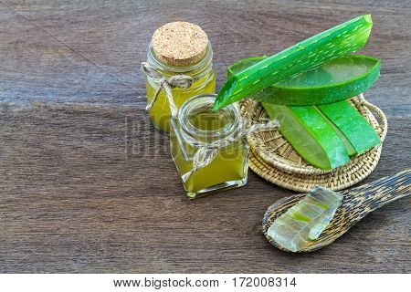 Fresh aloe vera gel on wooden spoon with aloe vera essential oil on wooden table