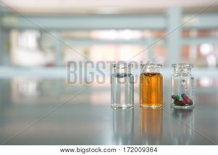 three vials with capsule pill orange and water solution in science laboratory background