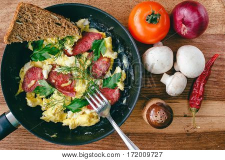Fresh cooked scrambled eggs in pan with sausage and herbs. Tomato onion chilli pepper mushrooms on wooden board top view