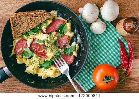 Fresh cooked scrambled eggs in pan with sausage and herbs. Tomato chilli pepper mushrooms on wooden board top view
