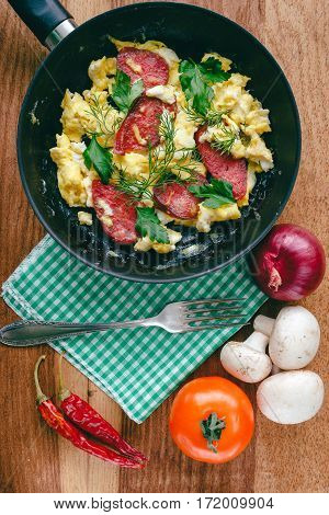 Fresh cooked scrambled eggs in pan with sausage and herbs. fork vegetables napkin on wooden board top view