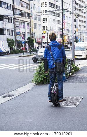 Japanese People Standing And Riding Unicycle  On Pathway Beside Traffic Road At Shinjuku City