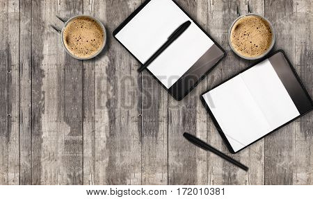 Notebooks with empty pages and mugs of coffee with foam