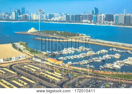 Abu Dhabi, United Arab Emirates - April 21, 2013: panoramic view of Marina of Abu Dhabi from Marina Mall Tower, shopping mall. Boats and luxury yachts docked at harbor. Skyline background.