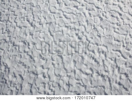Snow shaped by wind and weather. Nature background.