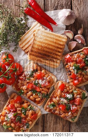 Toasts With Beans In A Tomato Sauce, Cheese And Herbs Closeup. Vertical Top View