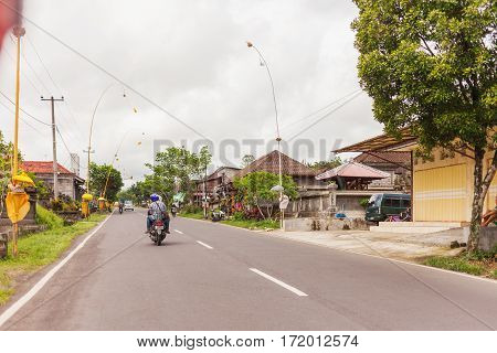 UBUD INDONESIA - January 26 2013. Religious decoration near houses on street. Road traffic in cloudy day.