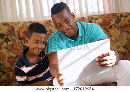 Happy black family at home. African american father and child playing game with tablet. Dad and son having fun with laptop computer
