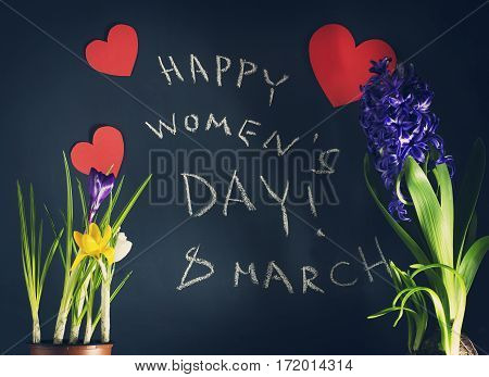 8 March, Happy Womens day with spring flowers and an inscription in chalk on a dark blue background.