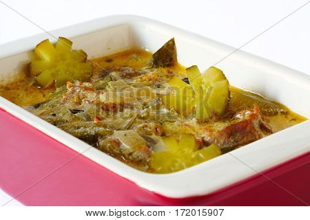 Meat stew with pickles. In red ceramic stewpot. On a white background. Close-up